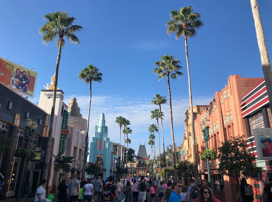Entrada da Disney Hollywood Studios, com palmeiras e prédios até o final da rua.
